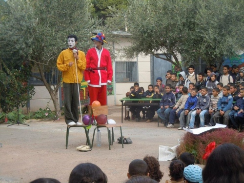 Two clowns stand on a chair in the village square, with somewhat esoteric props including old telephones and a length of rope.